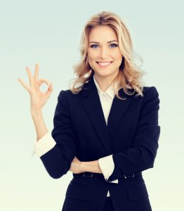Happy smiling beautiful young businesswoman showing okay gesture, with blank copyspace area for text or slogan
