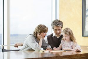 Parents helping their daughter draw